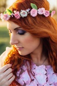 Jovem mulher ruiva com uma coroa de flores nos raios do pôr do sol