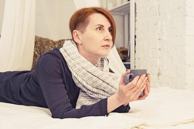 Jovem mulher ruiva deitada na cama com uma xícara de chá nas mãos e olhando pensativa