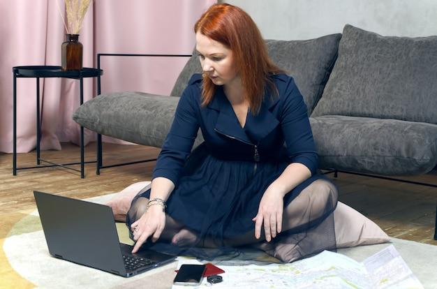 Jovem mulher ruiva está sentada no chão do apartamento dela e está planejando uma viagem com o laptop e o mapa de papel.
