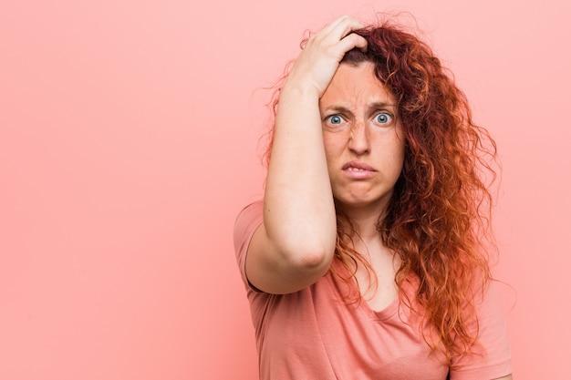 Jovem mulher ruiva natural e autêntica sendo chocada, ela lembrou reunião importante.