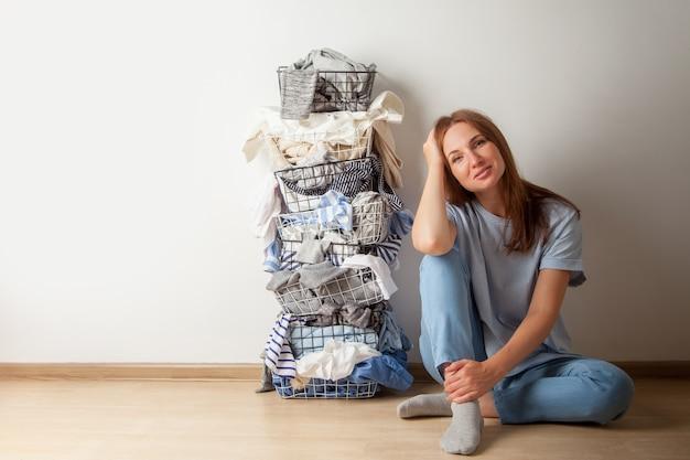 Jovem mulher ruiva sentada no chão de madeira com uma pilha de guarda-roupa e roupa de cama no cesto de roupa suja de metal.