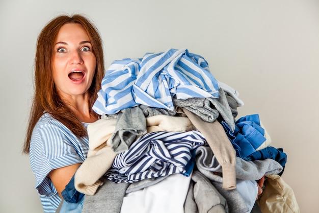 Jovem mulher ruiva surpresa carregando uma pilha de roupas bagunçadas em casa.