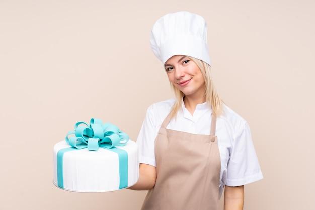 Jovem mulher russa com um bolo grande com expressão feliz