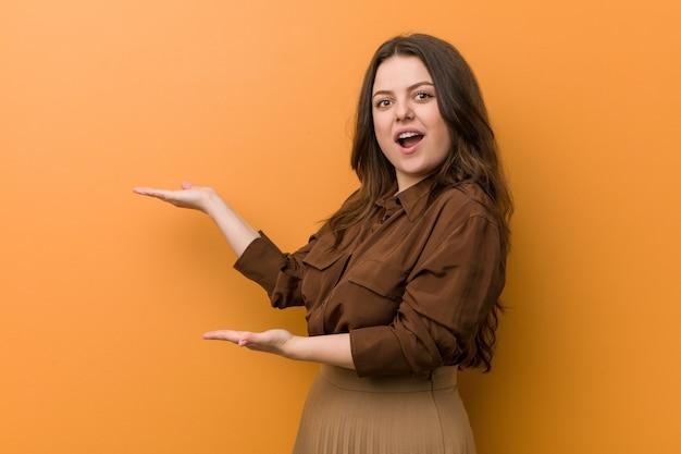 Jovem mulher russa curvilínea animado segurando um espaço de cópia na palma da mão.