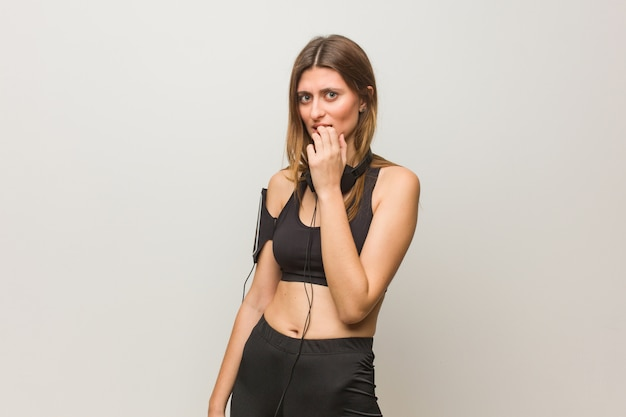 Jovem mulher russa fitness roer unhas, nervoso e muito ansioso