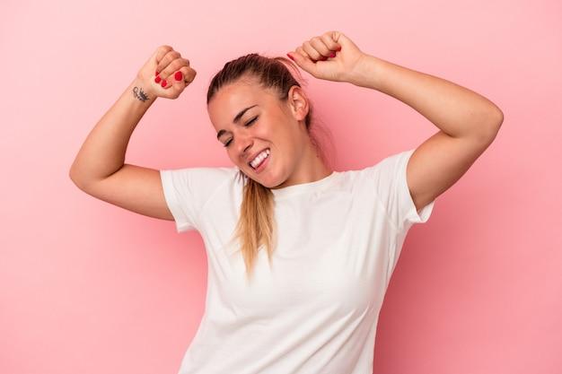 Jovem mulher russa isolada em um fundo rosa, comemorando um dia especial, pula e levanta os braços com energia.
