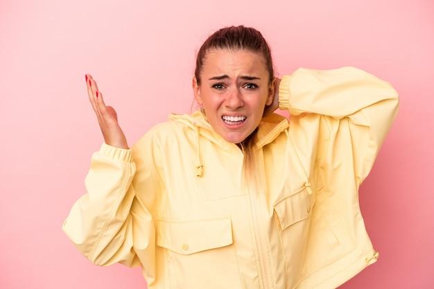 Jovem mulher russa isolada em um fundo rosa, gritando de raiva.