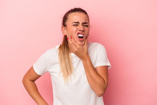 Jovem mulher russa isolada em um fundo rosa, tendo uma forte dor nos dentes, dor molar.