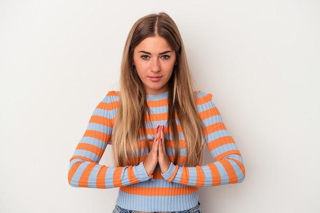 Jovem mulher russa isolada no fundo branco orando, mostrando devoção, pessoa religiosa em busca de inspiração divina.