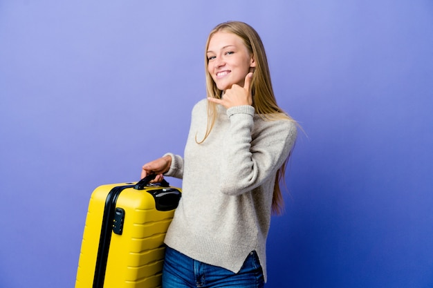 Jovem mulher russa segurando a mala para viajar, mostrando um gesto de chamada de celular com os dedos.