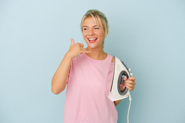 Jovem mulher russa segurando ferro isolado em fundo azul, mostrando um gesto de chamada de telefone móvel com os dedos.