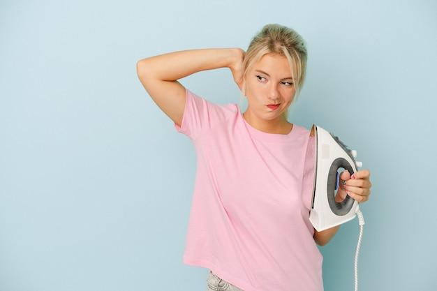 Jovem mulher russa segurando ferro isolado em um fundo azul, tocando a parte de trás da cabeça, pensando e fazendo uma escolha.