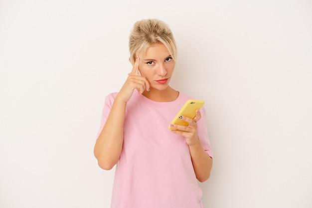 Jovem mulher russa segurando o telefone móvel isolado no fundo branco, apontando o templo com o dedo, pensando, focado em uma tarefa.