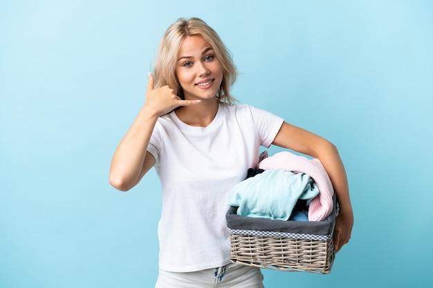 Jovem mulher russa segurando um cesto de roupas isolado na parede azul, fazendo gesto de telefone. ligue-me de volta sinal