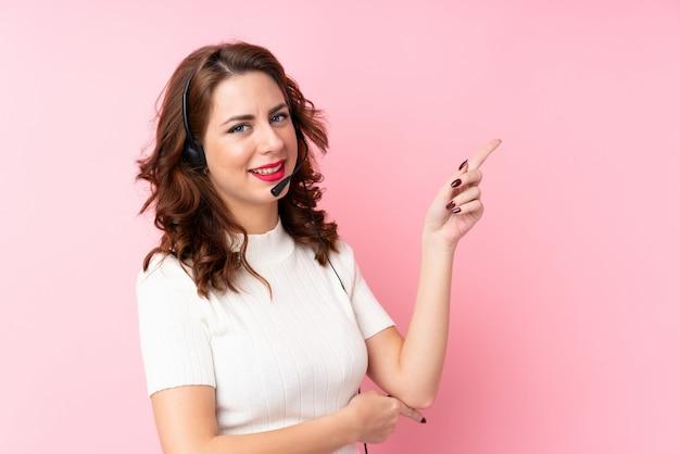 Jovem mulher russa sobre o lado apontador rosa isolado