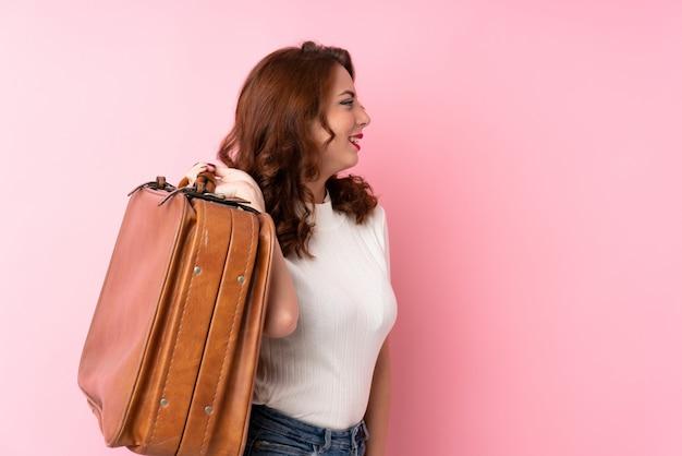 Jovem mulher russa sobre rosa isolada, segurando uma mala vintage
