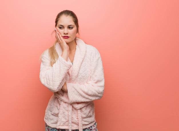 Jovem mulher russa vestindo pijama cansado e com muito sono