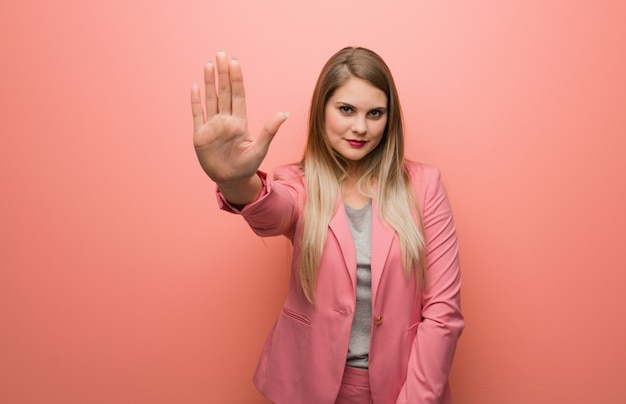 Jovem mulher russa vestindo pijama, colocando a mão na frente