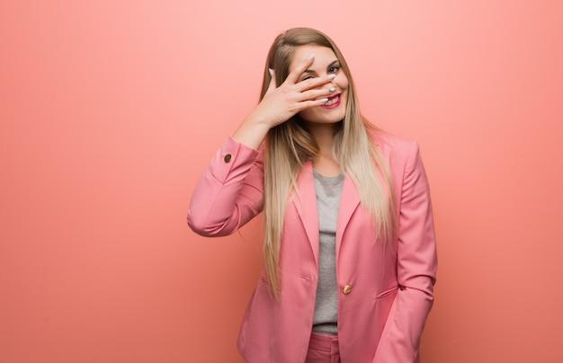 Jovem mulher russa vestindo pijama envergonhado e rindo ao mesmo tempo
