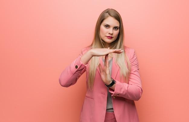 Jovem mulher russa vestindo pijama, fazendo um gesto de tempo limite