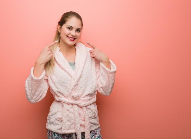 Jovem mulher russa vestindo pijama sorri, apontando a boca