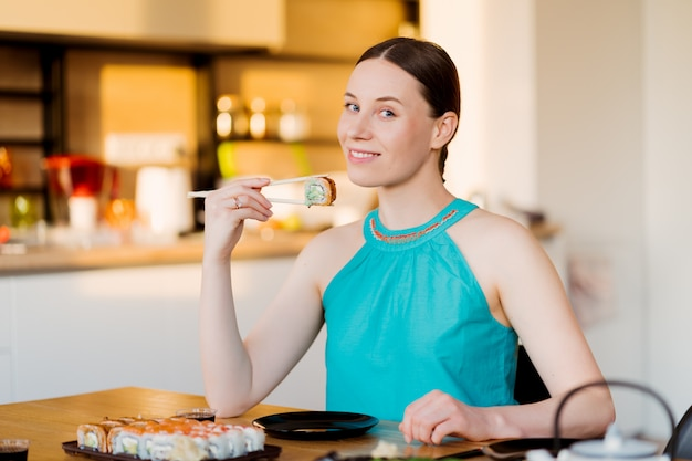 Jovem mulher saboreando seu sushi