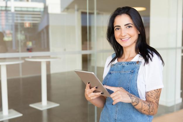 Jovem mulher satisfeita que guarda a tabuleta digital