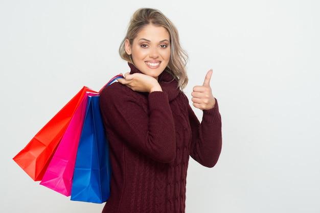 Jovem mulher satisfeita que guarda sacos de compras