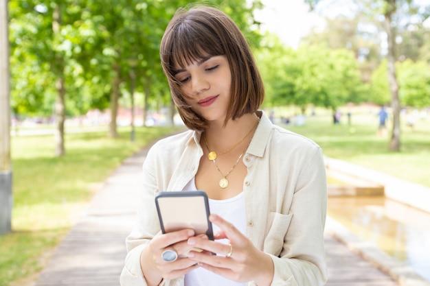 Jovem mulher satisfeita que usa o smartphone ao ar livre
