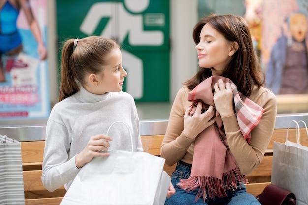 Jovem mulher satisfeita segurando novo lenço de cashmere pelo peito enquanto a linda garota olhando para a mãe durante o descanso no shopping