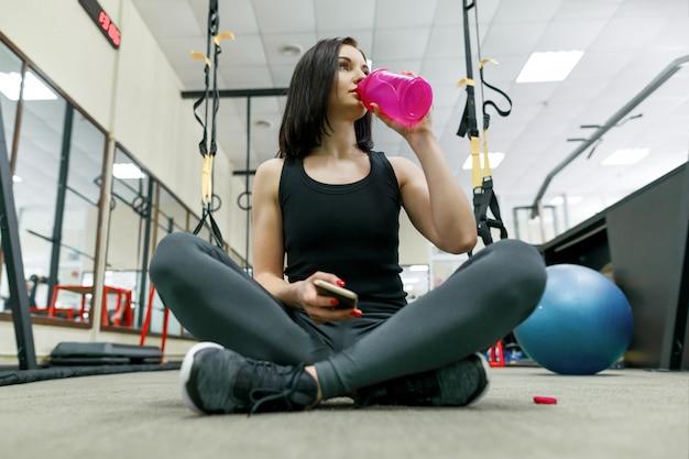 Jovem mulher saudável com água de garrafa descansando no ginásio
