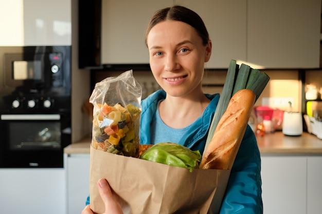 Jovem mulher saudável com sacos de compras em casa
