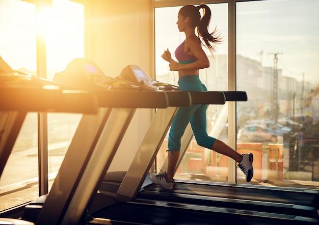 Jovem mulher saudável e atlética correndo em uma esteira perto da janela ensolarada no ginásio e ouvindo música.