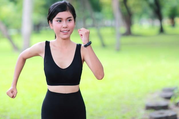 Jovem mulher saudável e desportiva, movimentando-se no parque