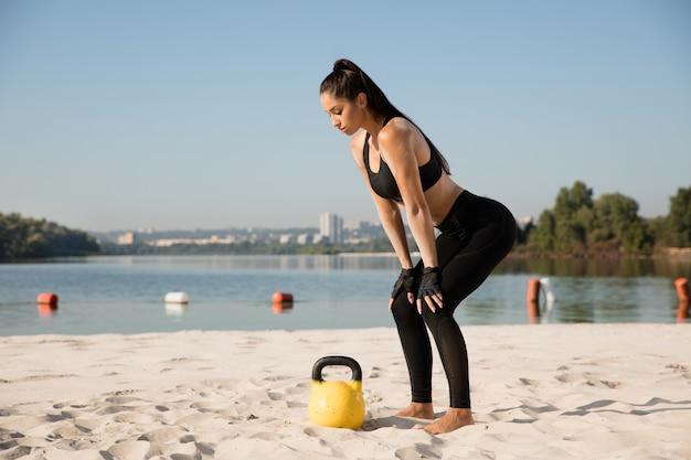 Jovem mulher saudável fazendo agachamentos com pesos na praia.