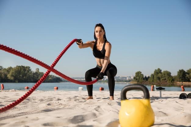 Jovem mulher saudável fazendo exercícios com cordas na praia