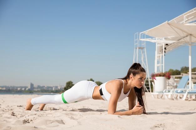 Jovem mulher saudável fazendo exercícios de alongamento na praia.
