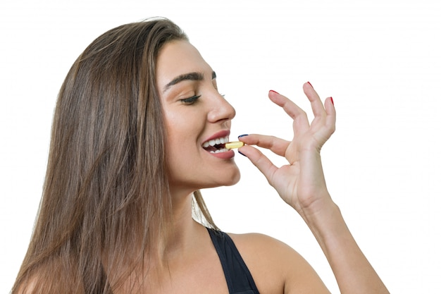Jovem mulher saudável no sportswear com vitamina d, e, um óleo de peixe ômega-3 cápsulas