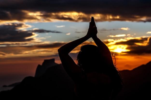 Jovem mulher saudável praticando ioga ao pôr do sol.
