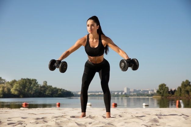 Jovem mulher saudável treinando a parte superior do corpo com pesos na praia.