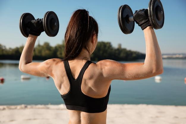 Jovem mulher saudável treinando parte superior do corpo com pesos na praia