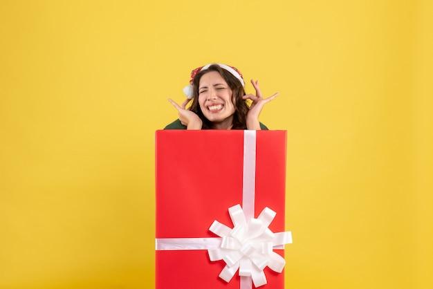 Jovem mulher se escondendo dentro da caixa de presente em amarelo de frente