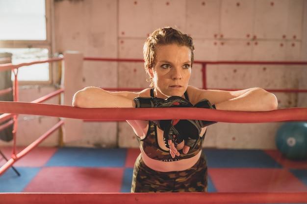 Jovem mulher se prepara para partidas de mma na gaiola. treinar em um salão de esportes
