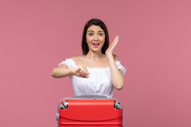 Jovem mulher se preparando para as férias de frente, verificando o tempo no fundo rosa no exterior