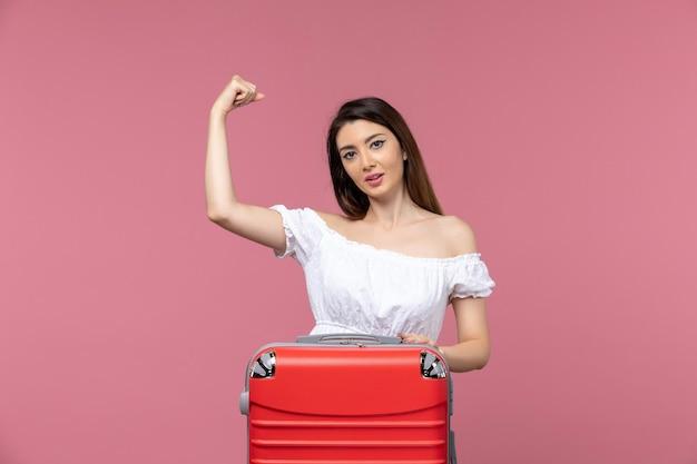 Jovem mulher se preparando para as férias e flexionando no fundo rosa no exterior viagem marítima viagem viagem viagem