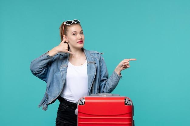 Jovem mulher se preparando para uma viagem de frente, posando no espaço azul