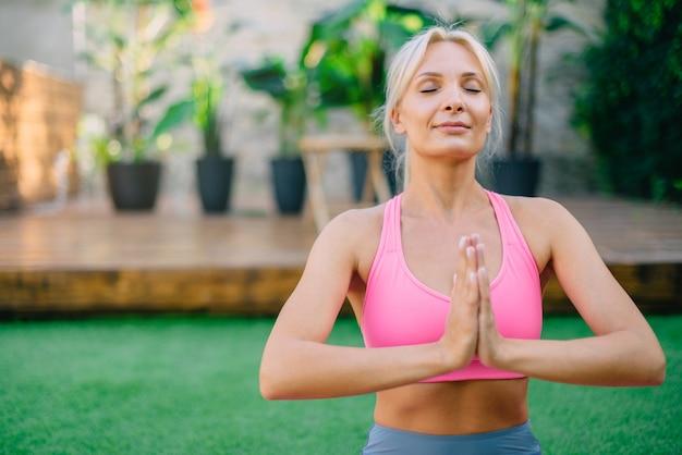 Jovem mulher se senta em posição de lótus na grama verde, conceito de ioga e meditação.