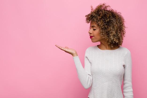 Jovem mulher se sentindo feliz e sorrindo casualmente, olhando para um objeto na mão do lado sobre parede rosa