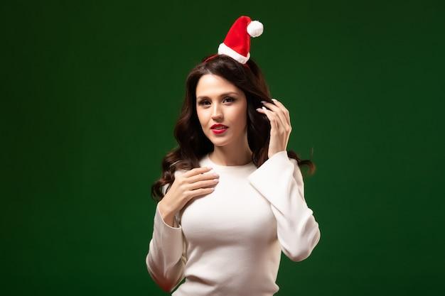 Jovem mulher sedutora com um lindo penteado festivo e maquiagem em um boné de papai noel