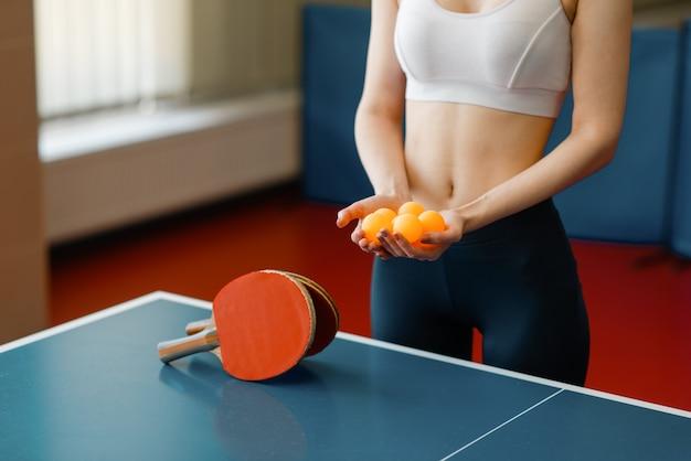 Jovem mulher segura bolas de pingue-pongue na mesa de jogo dentro de casa.